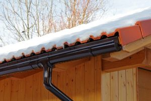 60249119 - a wooden roof with rain gutter and drainpipe in winter