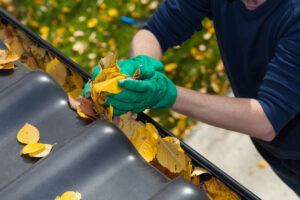 man cleaning out fall foliage from gutters